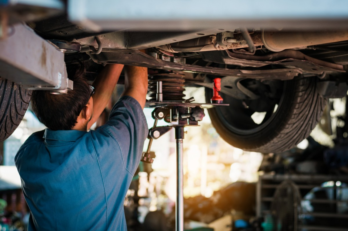 mechanic working on the suspension of a vehicle on a lift